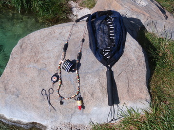 Fly fishing lanyard with tools and net attached.